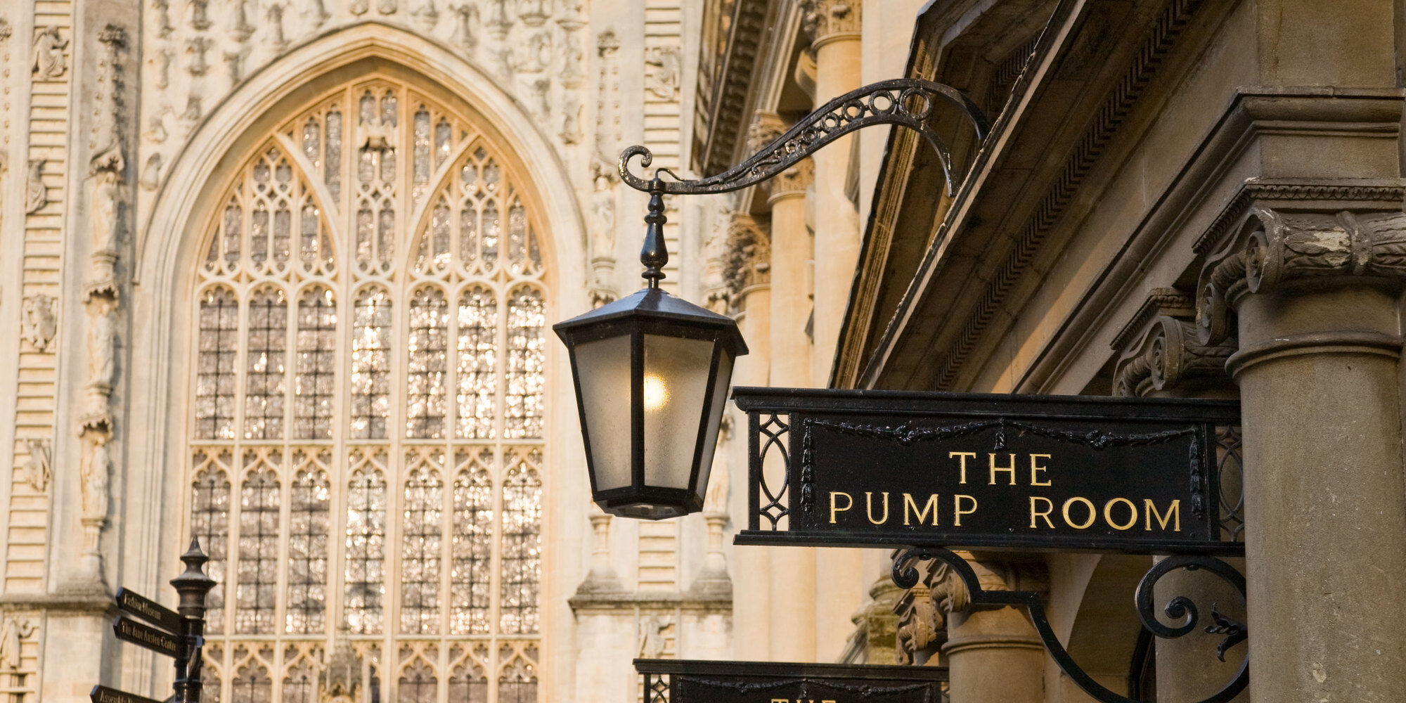 DC97JT Bath Pump rooms exterior signs and columns with the west window of Bath Abbey in the background.